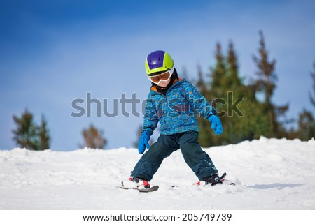 Small boy in ski mask and helmet learns skiing - stock photo