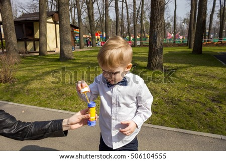 Small boy in the park is playing with bubbles and showing his tongue