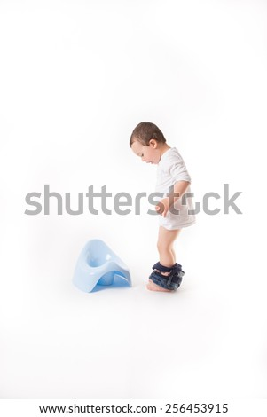 Small boy is wonering next to the blue potty