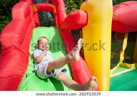 Small boy jumping down the slide on an inflatable bouncy castle - stock photo