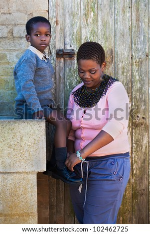 Small boy letting his mother fix his shoe lases - stock photo