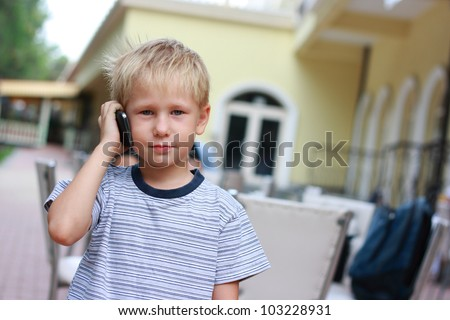 Small boy listening to a cellphone. - stock photo
