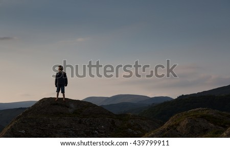 Small boy looking at scenery in evening light - stock photo