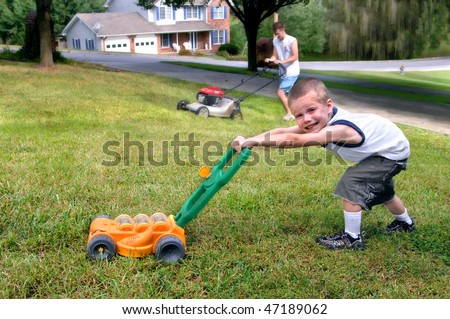 Small boy mows grass just like his dad.  He is grinning and pushing a toy lawn mower while dad mows with his. - stock photo