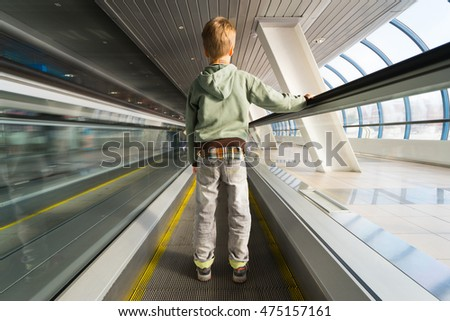 Small boy on escalator in airport. Back view.