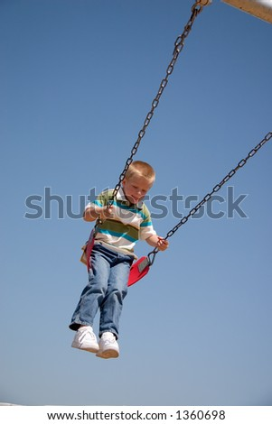 Small boy on playground swing - stock photo