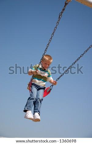 Small boy on playground swing - stock photo