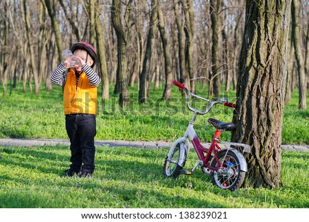 Small boy out cycling on his bicycle taking a break and standing in woodland enjoying a drink of refreshing bottled water - stock photo