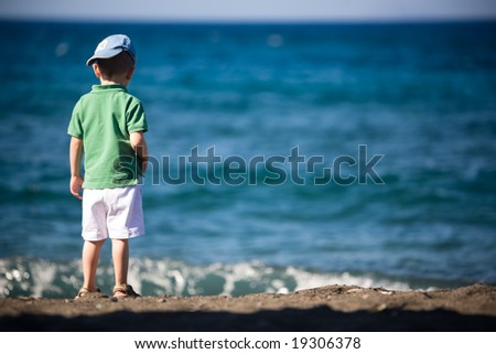 Small boy playing at volcanic black sand beach - stock photo