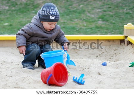 small boy playing in sandbox - stock photo