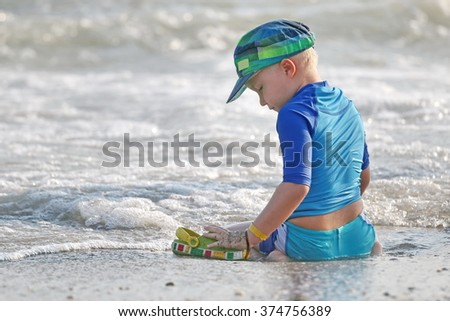 Small boy playing on the sand beach. - stock photo