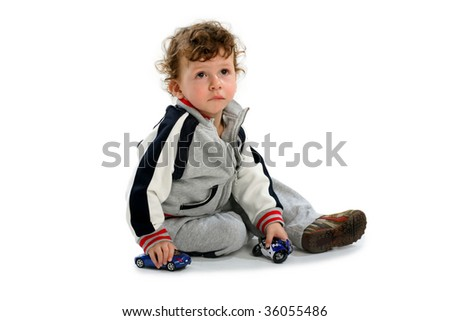 small boy playing toy sitting on the floor