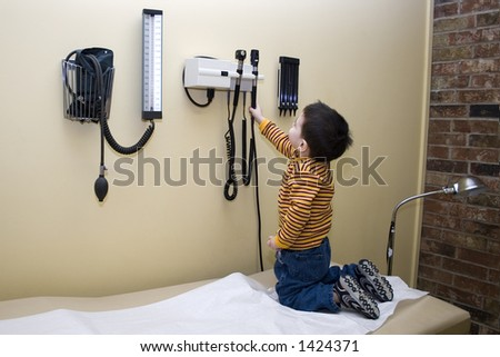 Small boy playing with exam equipment while the doctor is out. - stock photo