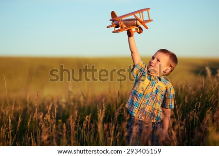 small boy playing with plane on meadow - stock photo