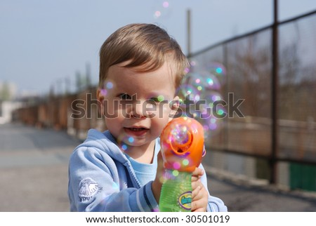 small boy playing with soap bubbles gun - stock photo