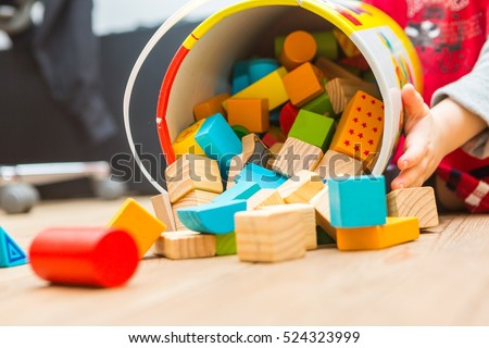 Small boy playing with wooden blocks on floor. Baby toy and child.
