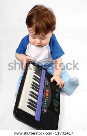 Small boy plays with the electronic piano