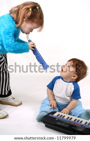 Small boy plays with the electronic piano. Girl plays on the pipe
