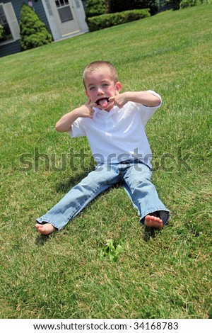 Small boy pulling a funny face - stock photo