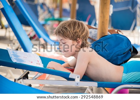 Small boy reading a book on a deck chair at the outdoor swimming pool
