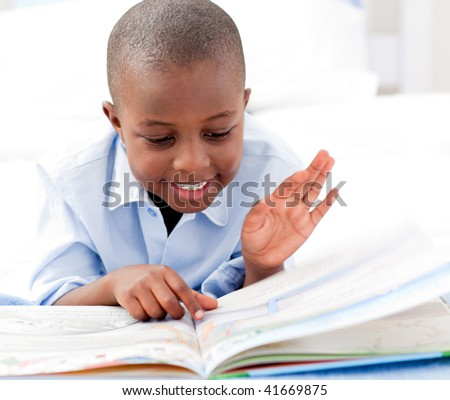 Small boy reading a book on his bed - stock photo