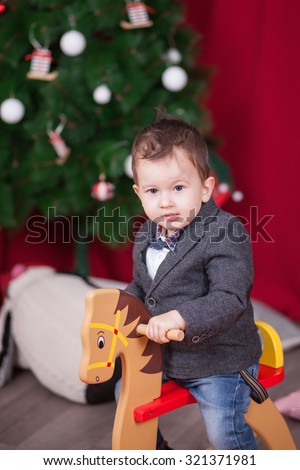 Small boy ride wooden rocking horse in front of christmas tree - stock photo
