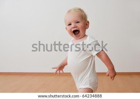 Small boy running around in house - stock photo
