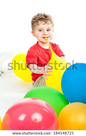 small boy sits around balloons isolated on white - stock photo