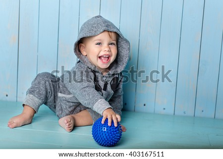 small boy sits, smiles and keeps the ball - stock photo