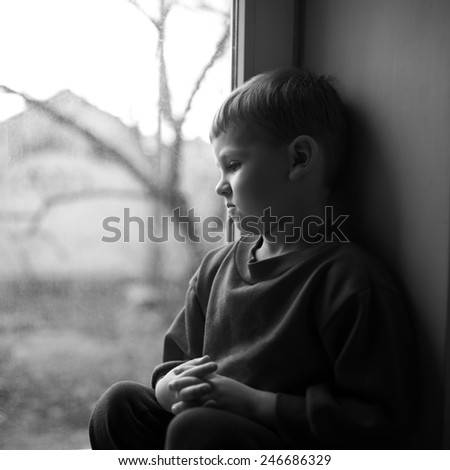 small boy sitting near window and thinking about something - stock photo