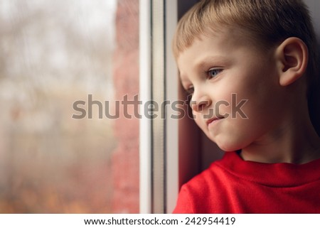 small boy sitting near window and thnking about something - stock photo