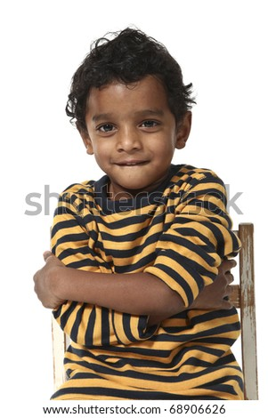 small boy sitting on a white background