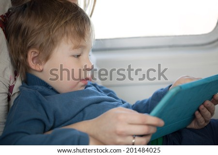 Small boy sitting on his mothers lap alongside a window looking at a tablet in an airplane as he travels on vacation, side view candid portrait - stock photo
