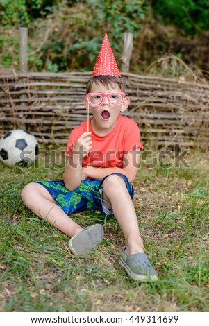 Small boy sitting on the grass in front of an old rustic garden fence playing with photo booth props holding a set of spectacle frames to his eyes