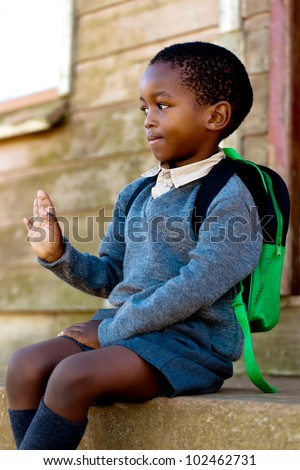 Small boy sitting on the steps waving for the people passing - stock photo