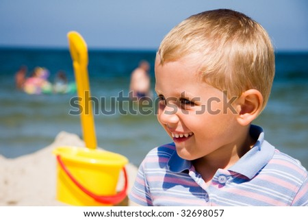 Small boy smiling on a sunny beach - stock photo
