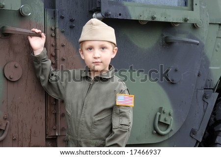 small boy soldier in front of a military truck, youth, young