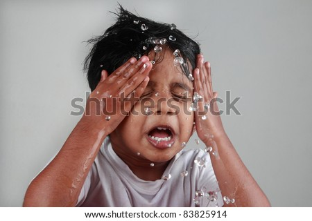 Small boy splashes water on his face - stock photo