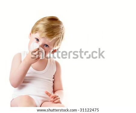 Small boy wipes a nose a napkin - stock photo