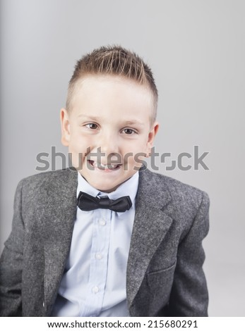 small boy with a hipster bow tie smiling