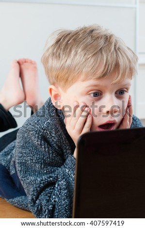 Small boy with a surprised expression from a webpage he has seen - stock photo
