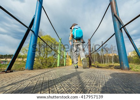 Small boy with backpack walking on the bridge. - stock photo