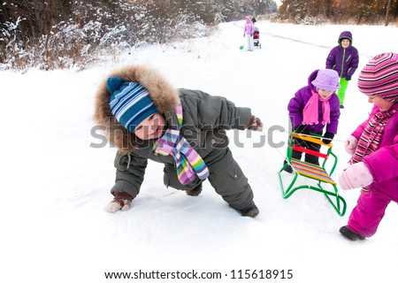 small boy with friends in the snow pulling sled hill - stock photo