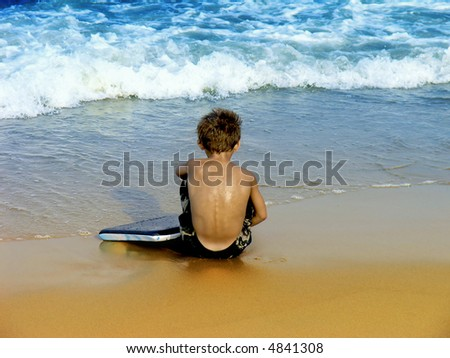 Small boy with his boogie board sitting at the edge of the surf at Virginia Beach. - stock photo