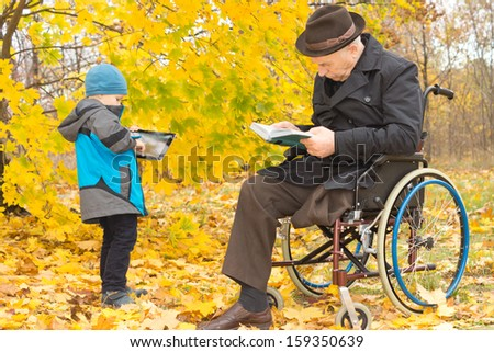 Small boy with his handicapped grandfather outdoors in a colourful fall garden with the old man sitting in his wheelchair reading while his grandson plays on a tablet computer - stock photo