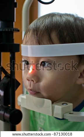 Small boy with slit lamp microscope for eye examination. - stock photo