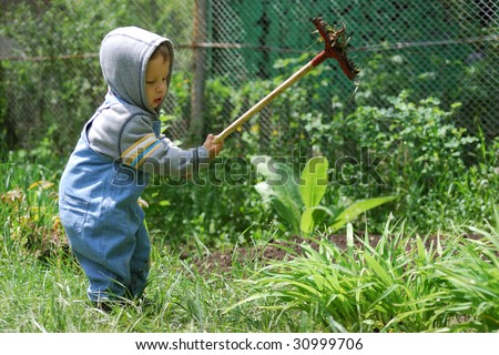 small boy with small rake - stock photo