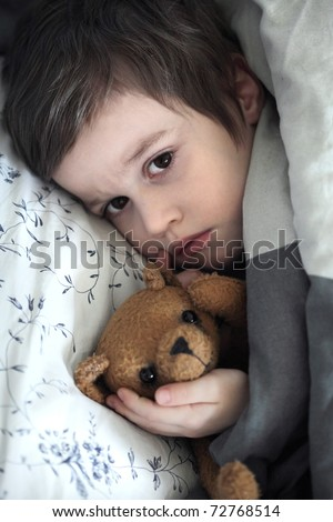 Small boy with teddy bear toy in the bed - stock photo