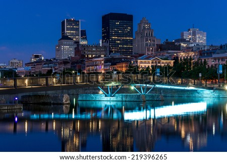 Small Bridge for Pedestrians with Basin Water, and in the background a part of the City of Montreal with a bit of digital noise. - stock photo