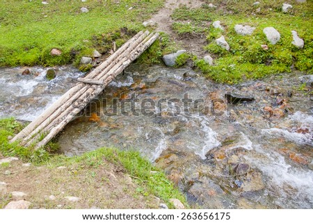 Small bridge over mountain stream - stock photo